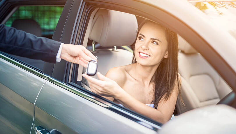 Woman buying a new car and receiving the keys